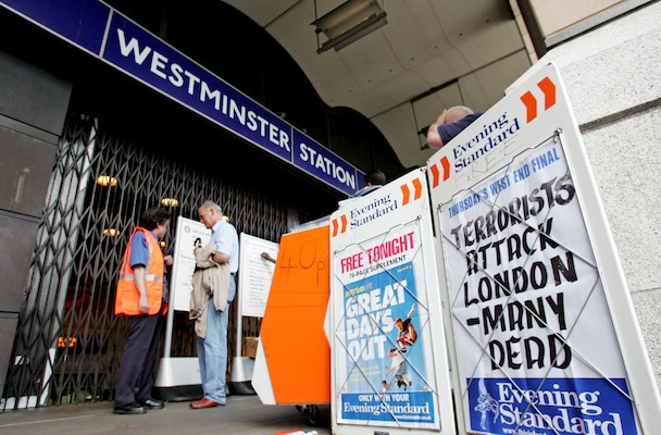 Member of London Underground staff talks to commuter outside Westminster Underground station in central ...